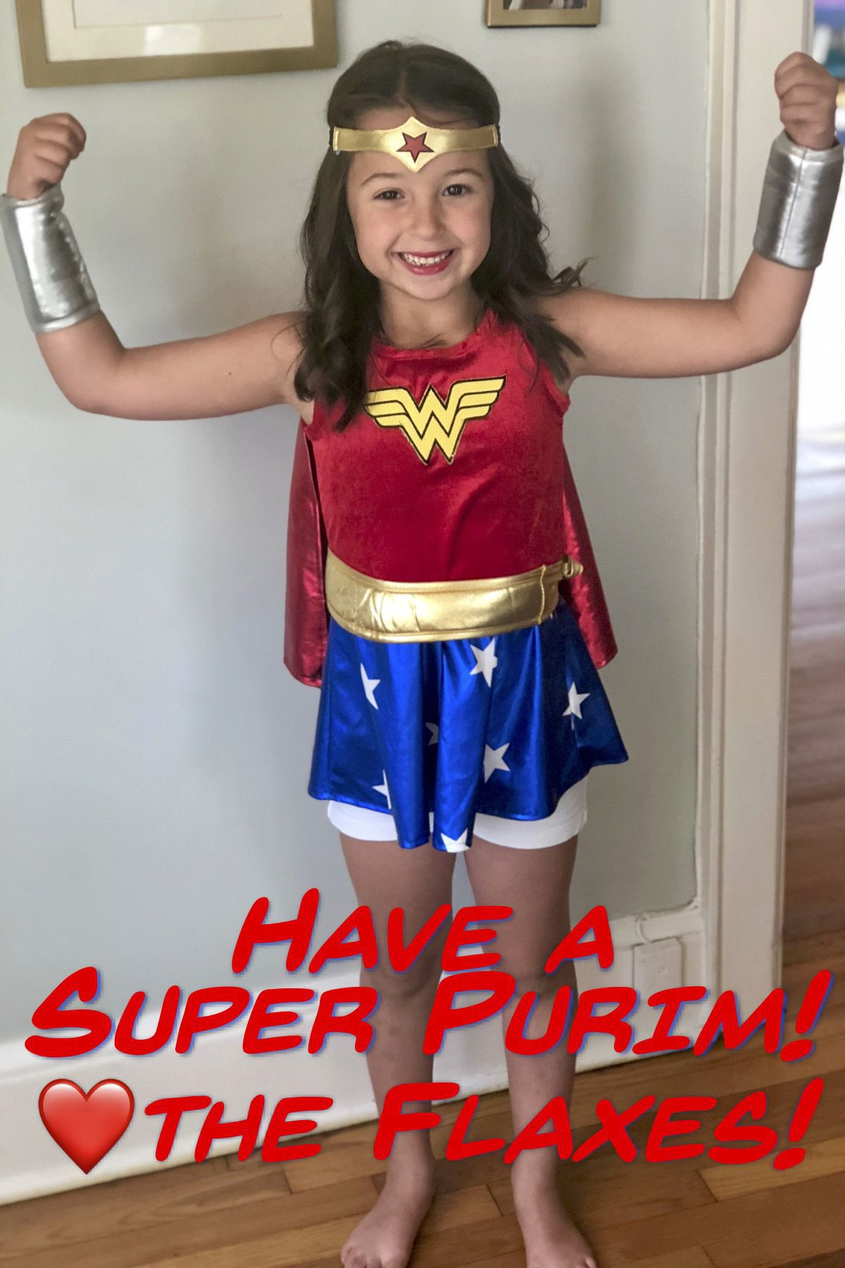 "Purim card showing my daughter wearing a Wonder Woman costume, smiling, with her arms in the air triumphantly. Caption along the bottom says ""Have a Super Purim! ❤️ the Flaxes!"""